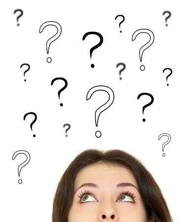 Kobieta patrząc na znaki zapytania nad głową na białym tle
