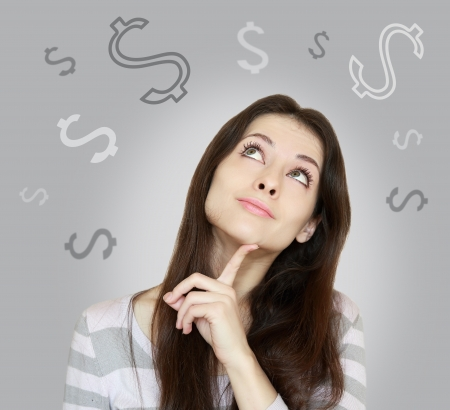Young woman thinking about money and looking up on grey background photo