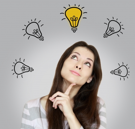 Happy thinking woman looking up on idea yellow bulb  Inspiration concept on grey background photo