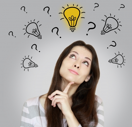 Thinking woman making dicision with looking up on idea bulb on grey background Stock Photo - 19423749