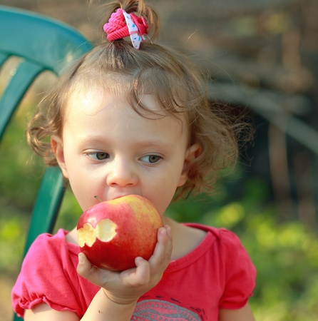 Baby girl eating big apple outdoor summer background Stock Photo - 19502939