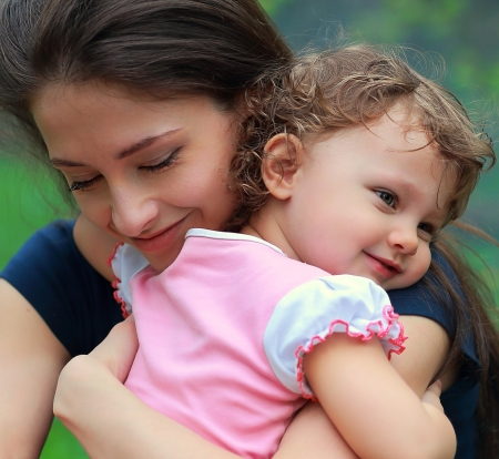 mother child: Happy mother and daughter cuddling outdoor green background  Closeup portrait