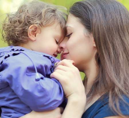 mother with child: Loving mother holding small happy girl and smiling  Closeup portrait face at face