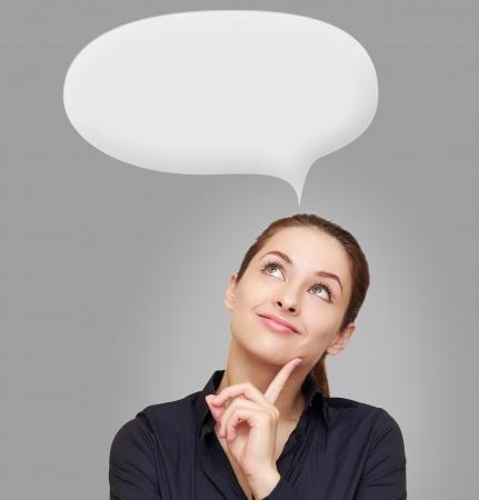 mujer pensativa: Pensamiento de la mujer joven mirando hacia arriba en la burbuja sobre fondo gris Foto de archivo