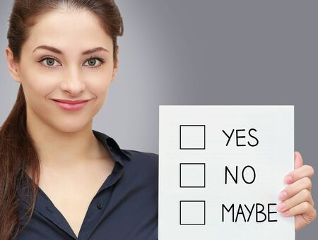 Business smiling woman holding blank with yes, no, maybe options on grey background Stock Photo - 19802646