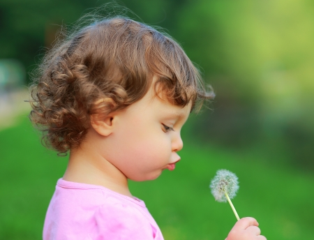Fun cute child blowing on dandelion flower on green summer background  Closeup portrait photo