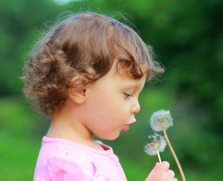 Beautiful girl looking on dandelion flower on green summer background  Closeup portrait photo