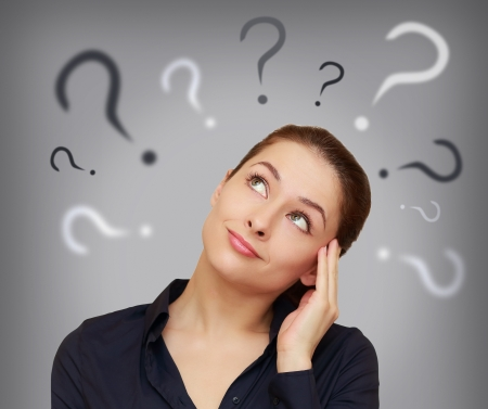confusing: Beautiful business woman with question mark above the head looking up on grey background Stock Photo