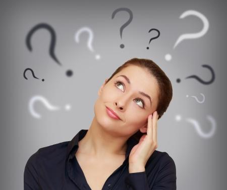 Mooie zakelijke vrouw met vraagteken boven de hoofd kijken up op grijze achtergrond Stockfoto