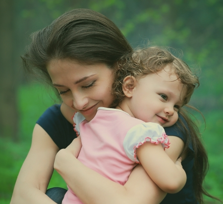 hugging: Happy loving mother and girl cuddling outdoor summer background  Closeup tender and love portrait