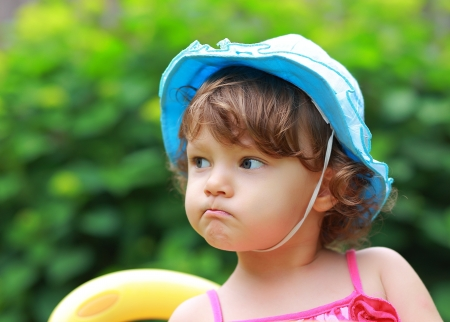 Angry fun girl looking in blue hat on summer green background photo
