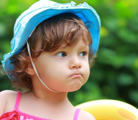 angry baby: Angry baby girl looking in blue hat on summer background  Closeup portrait Stock Photo
