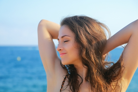Beautiful woman relaxing with closed eyes on blue sea background photo