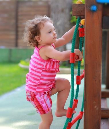niño trepando: El pequeño niño niña subiendo en los niños la actividad escalera al aire libre Foto de archivo