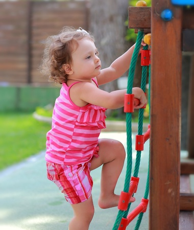 Small girl child climbing up on children activity ladder outdoors photo