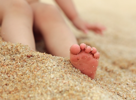 feet in water: Small baby feet on the sand background