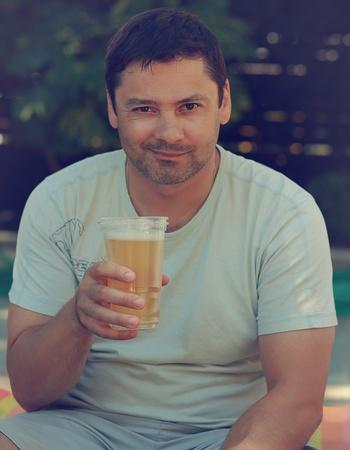 man drinkt bier: Knappe lachende man drinkt bier buiten achtergrond