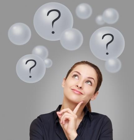 frau denken: Denken Business-Frau blickte auf viele Blasen mit Fragezeichen auf grauem Hintergrund