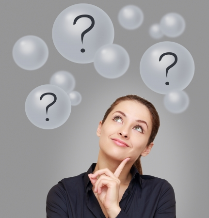 Thinking business woman looking up on many bubbles with question mark on grey background Stock Photo