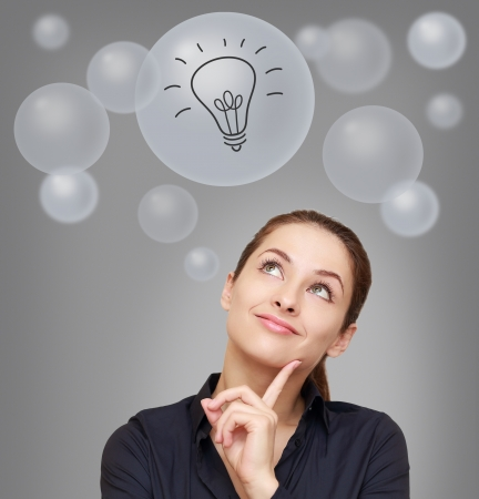 Thinking smiling woman looking up on many bubbles with idea bulb sign on grey background photo