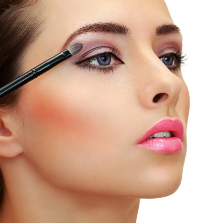 Eyes makeup  Brush applying eye shadows on beauty woman face  Closeup isolated portrait photo