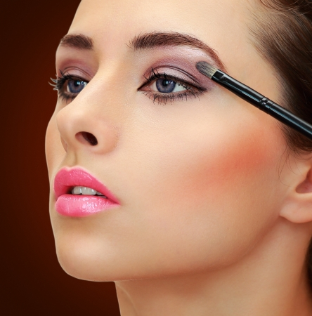 eyeshadow: Brush applying eye shadows on beauty woman face  Closeup portrait on brown background