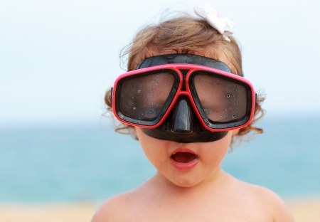 swim mask: Surprising baby girl in diving mask looking fun on blue sea background Stock Photo