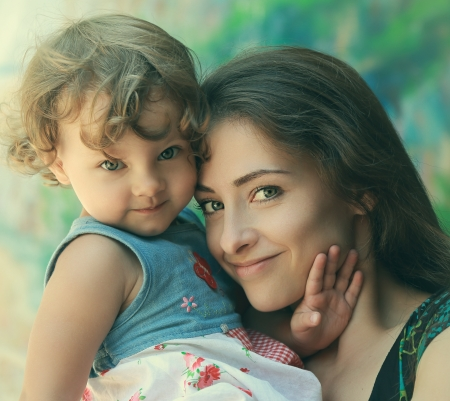 Beautiful happy mother and fun kid girl cuddling  Closeup tender portrait photo