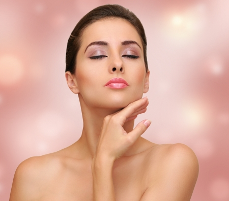 clear skin: Beautiful woman touching face clean skin on pink background