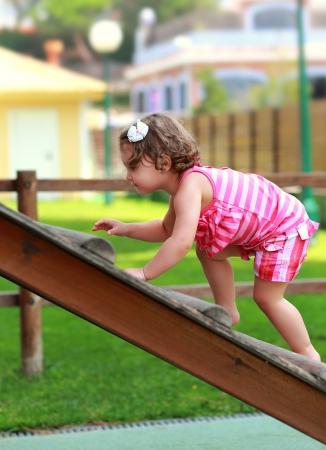 niño trepando: Bebé giri subir en la escalera de madera del niño en el fondo de verano