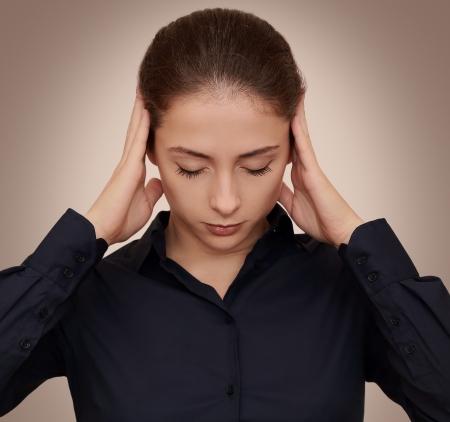 mente humana: Mujer de negocios pensando duro con concentraci�n holding manos la cabeza sobre un fondo oscuro