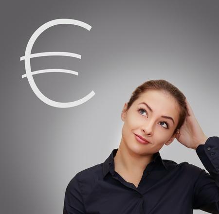 mujer pensativa: Mujer de negocios pensando en el dinero con el signo euro cerca de ella en el fondo se