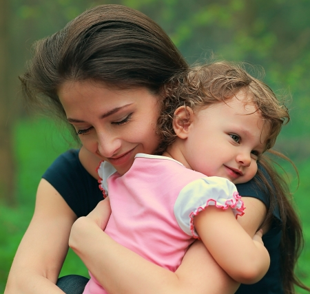 two women hugging: Beautiful happy mother hugging baby girl with love outdoors summer background  Closeup tender portrait