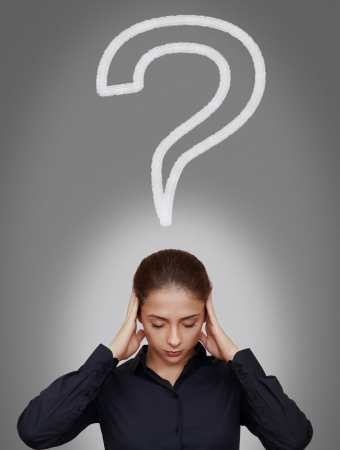 Business woman thinking hard with question sign above head on grey background photo