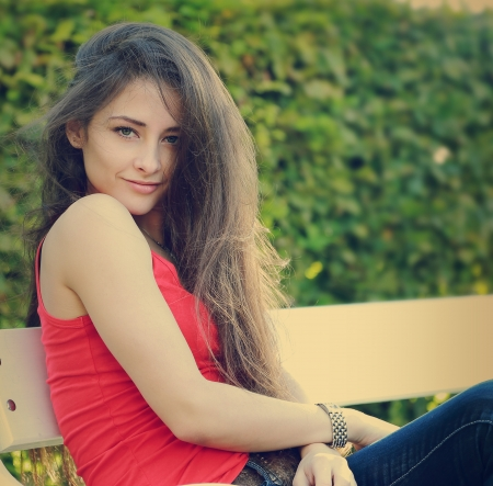 Beautiful sexy female model sitting on bench and looking sexy  Retro portrait photo