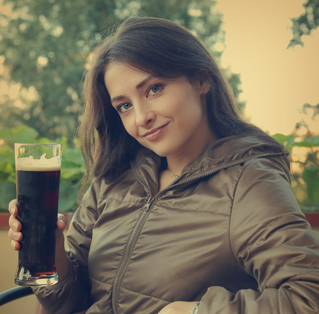 Smiling happy woman drinking dark beer on terrace cafe  Closeup vintage portrait  photo