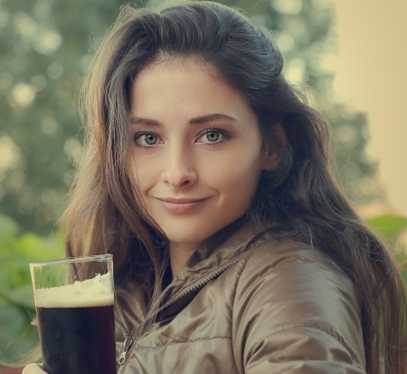 Beautiful woman drinking dark beer   photo