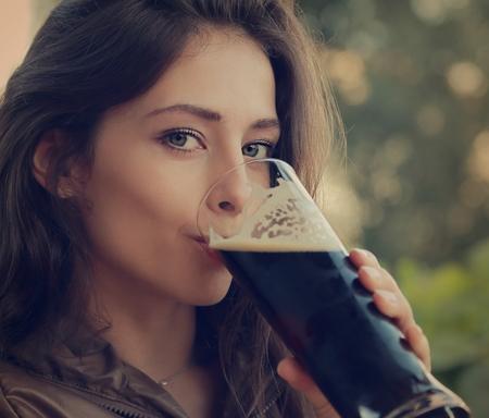 Woman drinking dark fresh beer outdoor and enjoying  Closeup vintage portrait Stock Photo