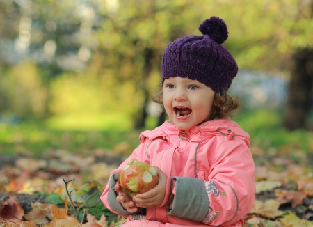 Happy baby in hat sitting on autumn background and eating big tasty apple photo