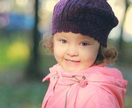 Funny smiling child in hat outdoors autumn background  Closeup portrait photo
