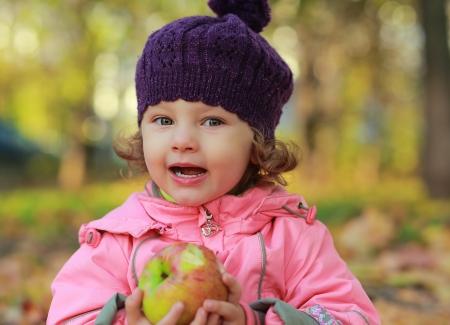 Funny kid girl eating apple on bright autumn  photo