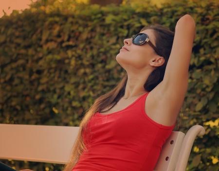 Ontspannende mooie vrouw in openlucht park achtergrond opzoeken Stockfoto