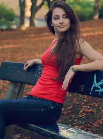 Sexy girl sitting on the bench in the park and thinking  Vintage portrait photo