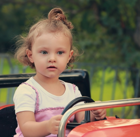 funny car: Funny thinking kid girl driving car in recreation park on summer background  Closeup portrait Stock Photo