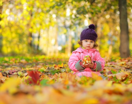 Cute small child sitting on autumn bright colorful foliage and holding apple photo