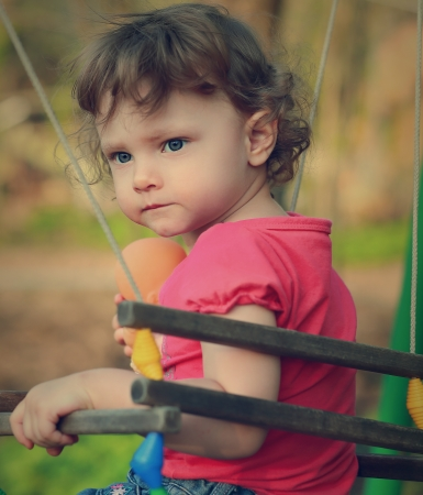 Serious cute baby thinking on swing  Closeup portrait photo