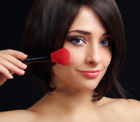 Woman applying blusher the big red brush  Closeup portrait photo
