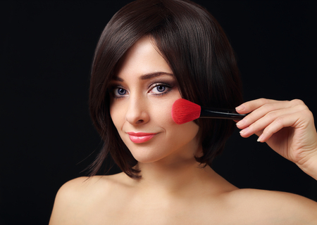 Beauty woman applying makeup big brush on black background photo