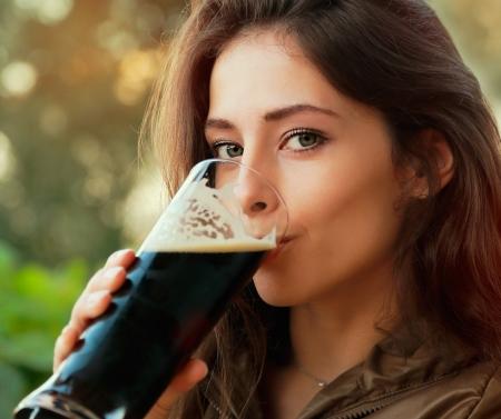 Szczęśliwa kobieta pije ciemne piwo i patrząc na zewnątrz Portret przeznaczone do walki radioelektronicznej Zdjęcie Seryjne