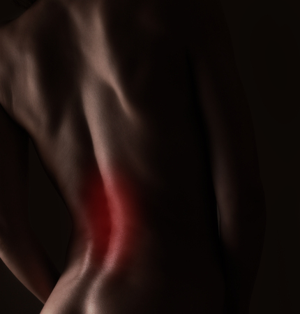 Pain in sporty woman back  Closeup portrait photo